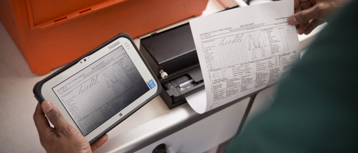 A healthcare paramedic is using the Brother PJ7 mobile printer to print out hospital patient pre-admissions from the ambulance via a tablet computer.