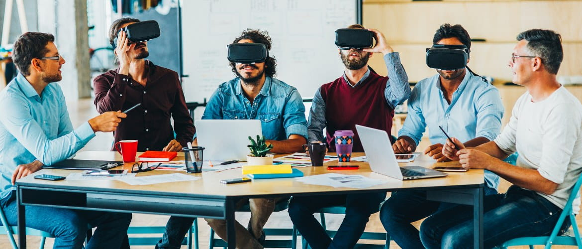 Office of the future - technological backbone image depicting six office workers using VR augmented reality headsets while working through a business meeting