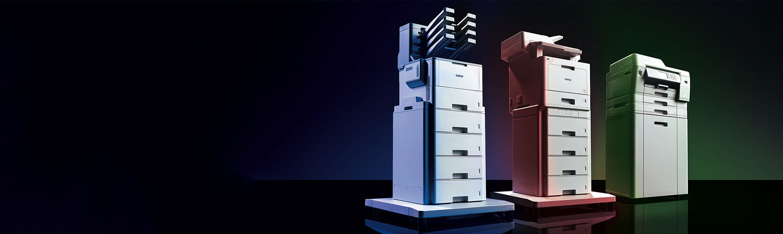 Brother HL-L9310CDW, MFC-L9570CDW ir MFC-J6947DW profesionalių spausdintuvų grupė juodame fone apšviesti mėlynai, raudonai ir žaliai.