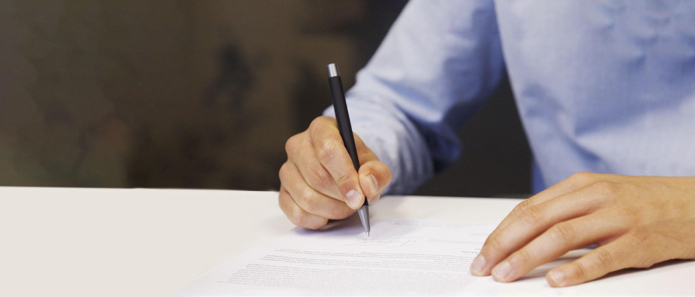 Man wearing blue shirt signing document