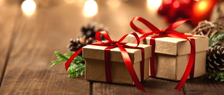 Kalėdinės dovanos su užrišta raudona satino juosta tarp kankorėžių