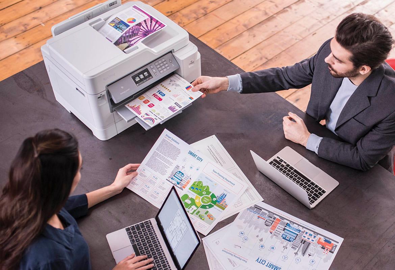 Vyras ir moteris sėdi prie spausdintuvo