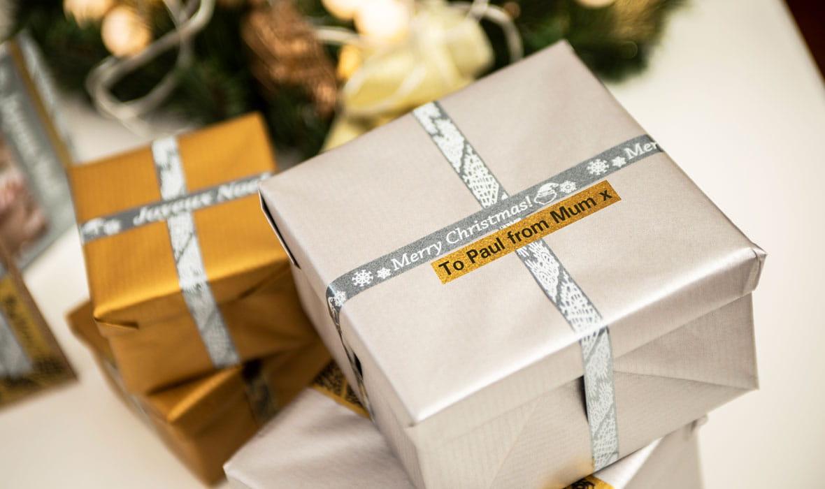 Dvi kalėdinės dovanos pažymėtos blizgiomis sidabrinėmis etiketėmis su personalizuota žinute atspausdintomis Brother P-touch etikečių spausdintuvu