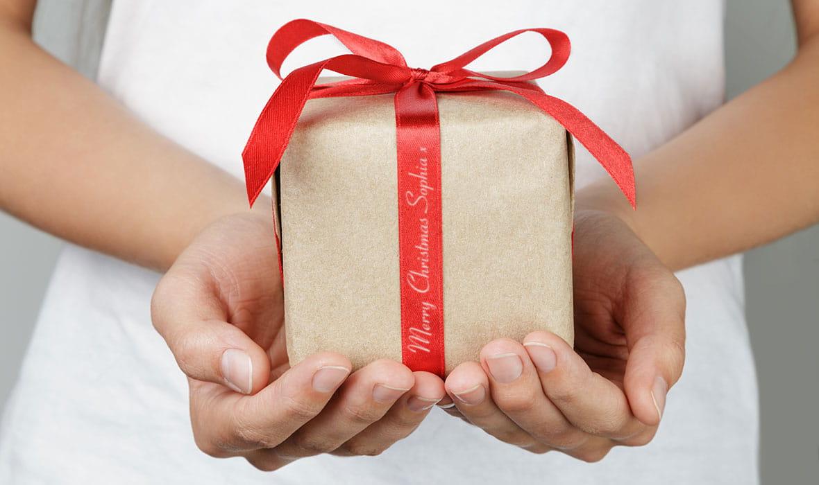 Kalėdinė dovana gražiai perrišta raudonu kaspinu su personalizuota žinute atspausdinta ant juostos