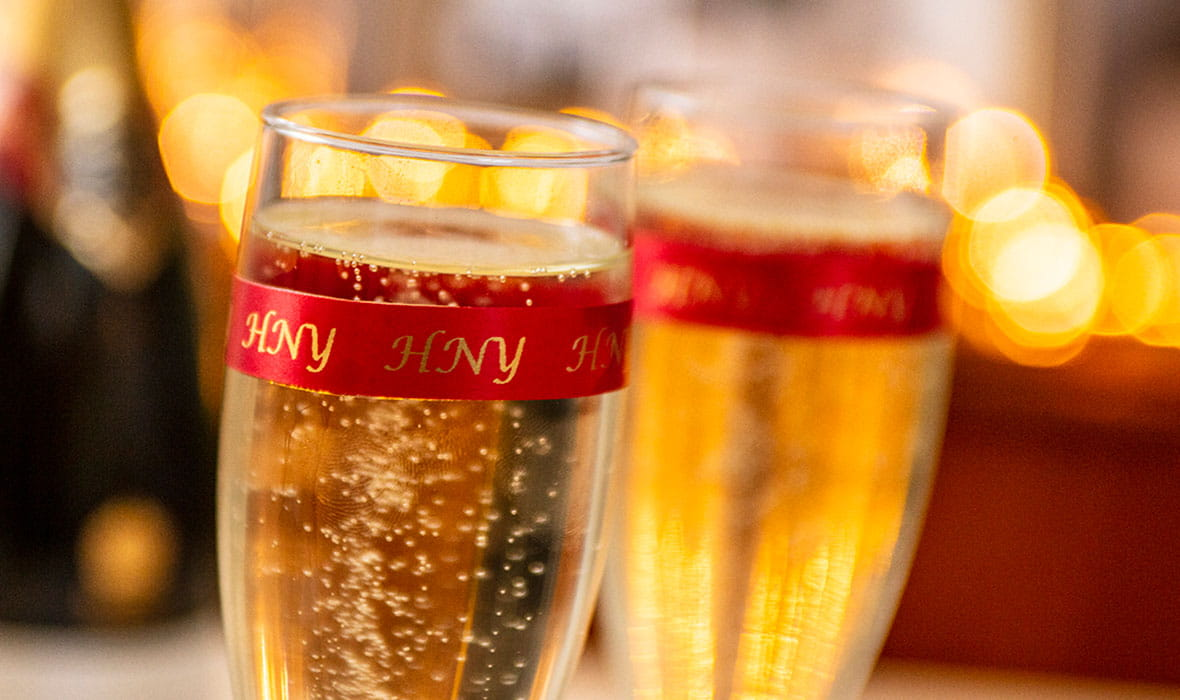 """Dvi šampano taurės aprištos Brother satino juosta su užrašu """"Laimingų Naujųjų metų"""""""