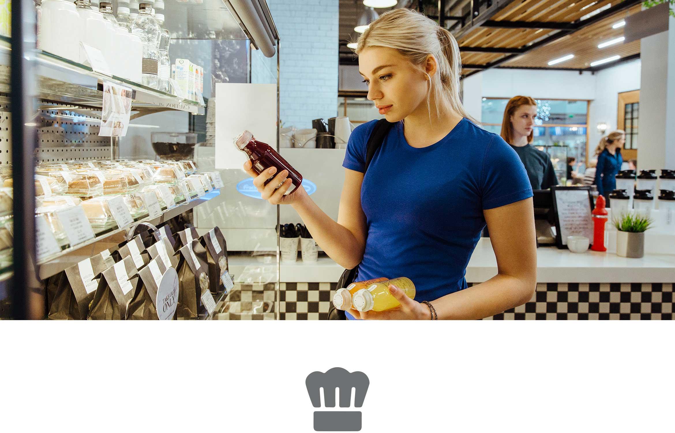 Woman with blond hair wearing blue tshirt looking at a juice bottle holding sandwich