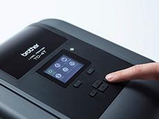 TD-4T desktop label printer screen close up with finger pressing button