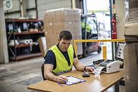 Vyras sandėlyje su nešiojamu kompiuteriu spausdina paskirstymo etiketę TD4d etikečių spausdintuvu