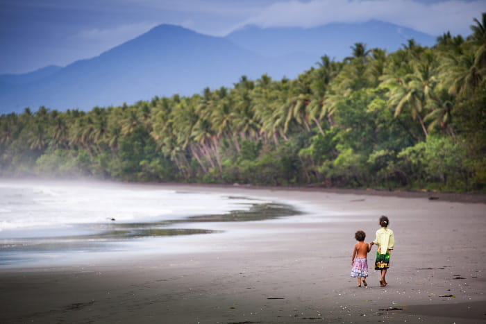 Woman and child walking on a beach island surrounded by trees